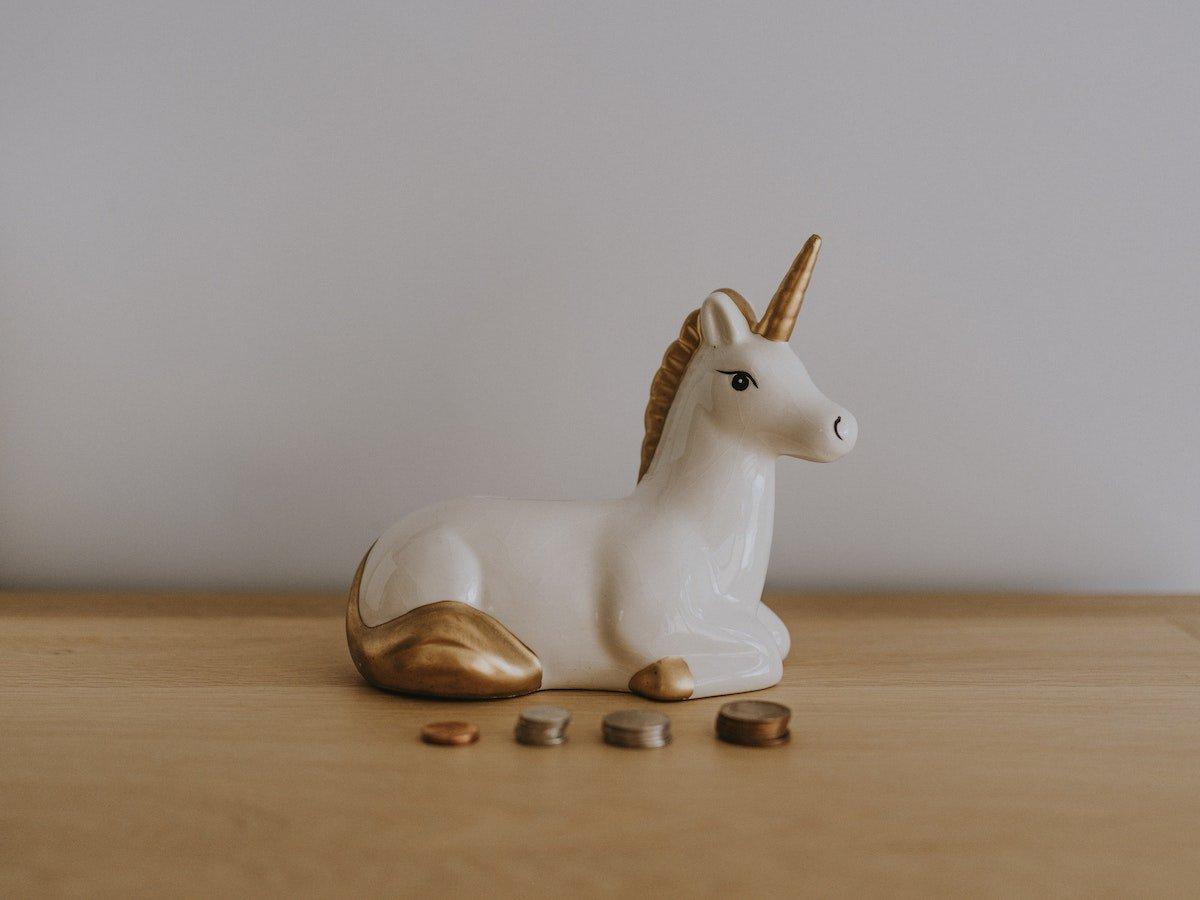 A small unicorn statue sitting on a table with spare change